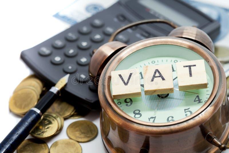 在闹钟和堆硬币的VAT词 库存照片