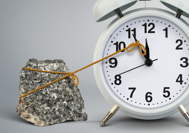 在闹钟的时间路过石头,延迟概念 库存照片