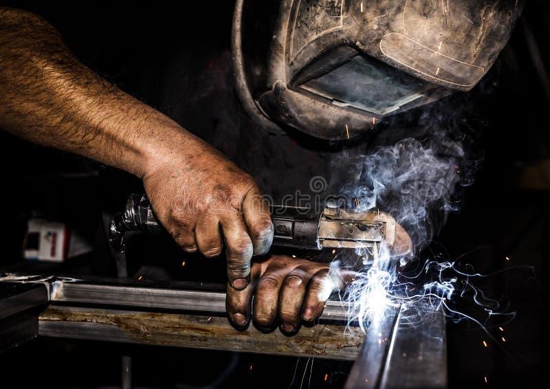 在防毒面具焊接金属和火花金属的Profesional焊工 免版税库存图片