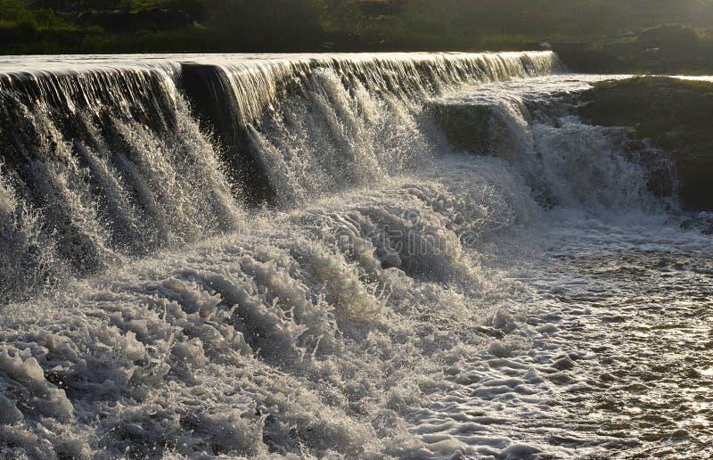 在防洪坝的人为水秋天有流动的水的在印地安村庄 库存照片