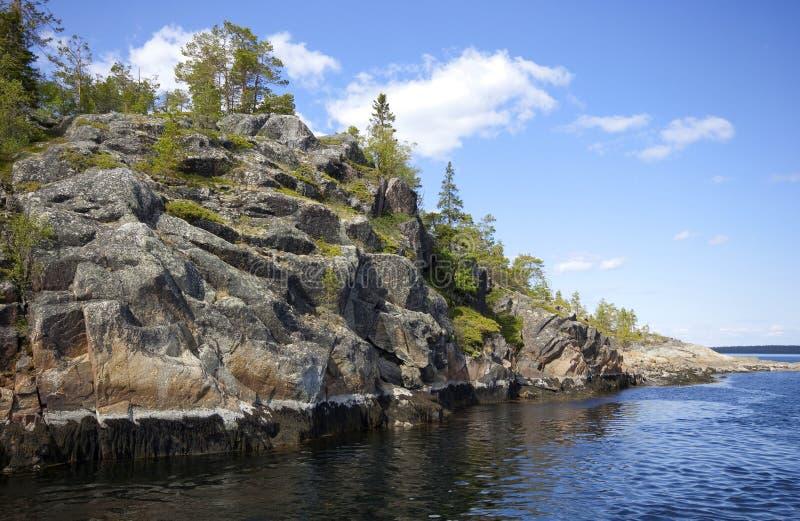 在阳光下,花岗岩岛陡峭的岩石岸, 库存图片