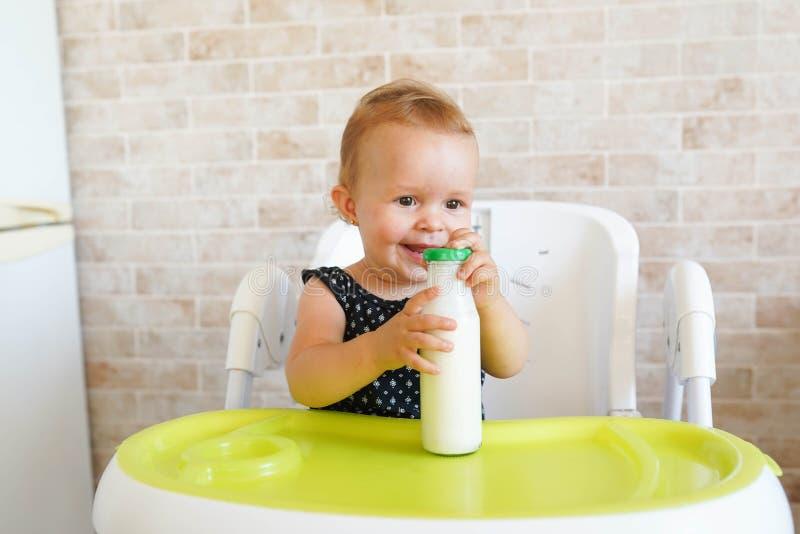 在阳光明媚的现代厨房里盛放奶瓶,为孩子们准备营养晚餐 免版税库存图片