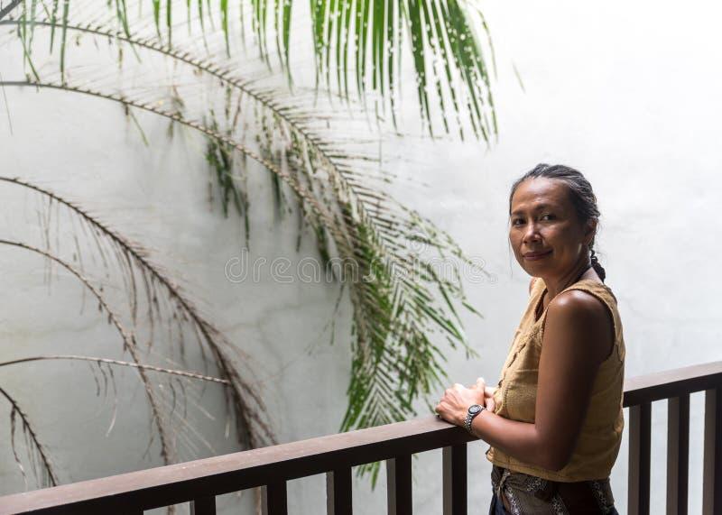 在阳台的亚洲妇女身分有后边白色墙壁和树的 免版税库存图片