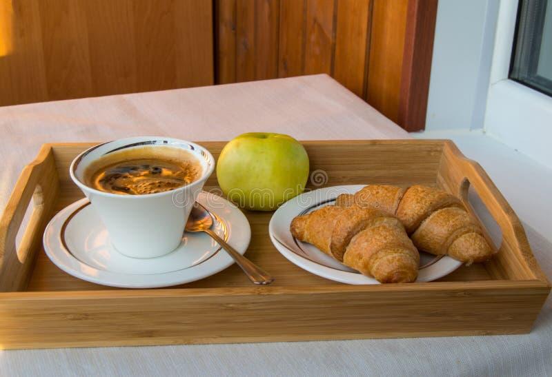 在阳台的可口早餐在阳光下,用咖啡,新月形面包,在一个木盘子的苹果计算机 免版税库存照片