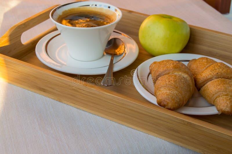 在阳台的可口早餐在阳光下,用咖啡,新月形面包,在一个木盘子的苹果计算机 免版税库存图片