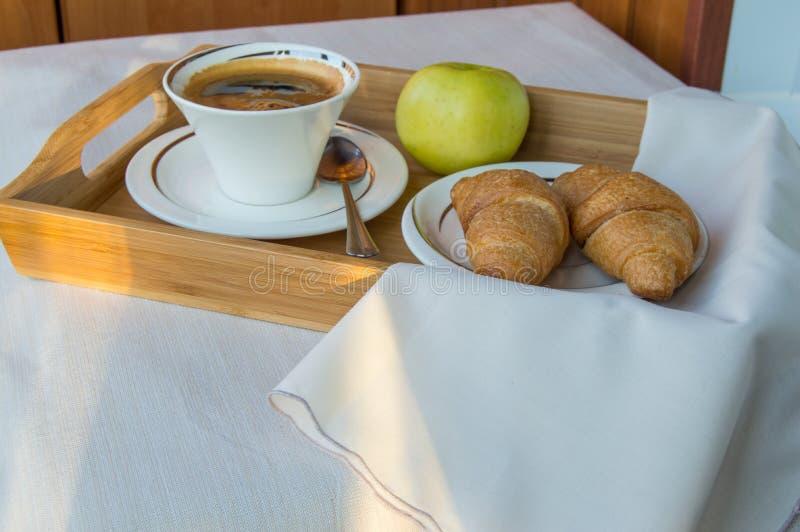 在阳台的可口早餐在阳光下,用咖啡,新月形面包,在一个木盘子的苹果计算机 库存图片