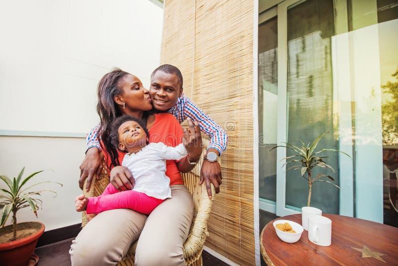 在阳台的可爱的非洲家庭 库存照片
