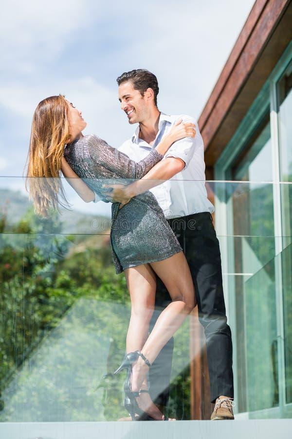 在阳台的浪漫年轻夫妇跳舞手段的 库存照片