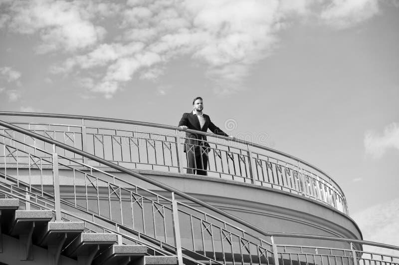 在阳台的确信的商人立场多云蓝天的 室外的礼服的人 查找的远期 认为 库存照片