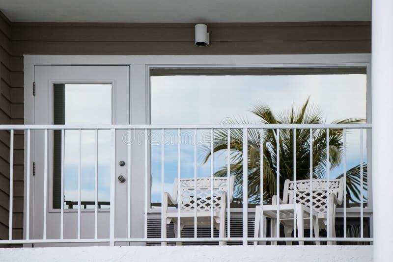 在阳台窗口反映的棕榈树 免版税库存照片