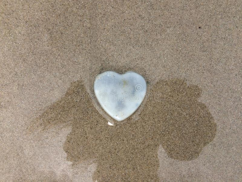 在阴影和沙子海滩的心脏石头 免版税库存照片