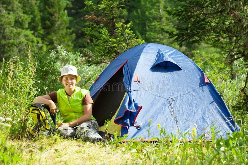 在阵营帐篷前面的愉快的远足者 库存照片