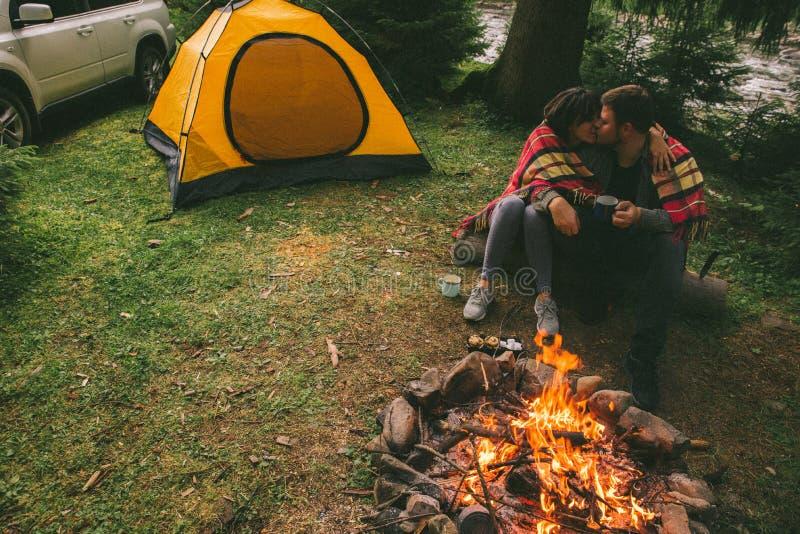 在阵营火和饮用的茶附近结合坐和讲故事 帐篷和suv在背景 图库摄影