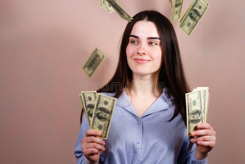 在阵雨下的幸运的富有的妇女身分从金钱 免版税库存照片