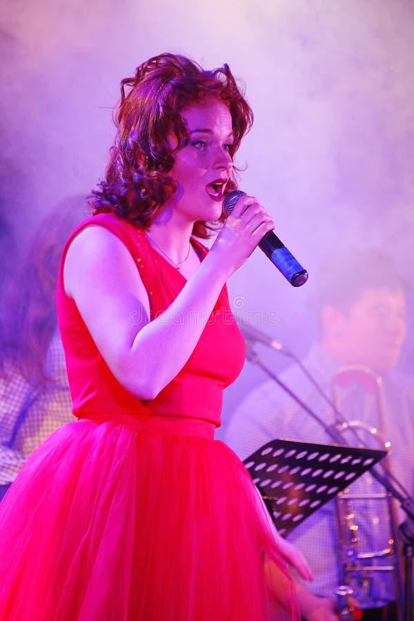 在阶段、音乐家流行音乐石小组薄荷和歌手安娜Malysheva 红色朝向的爵士乐岩石女孩唱歌 库存图片