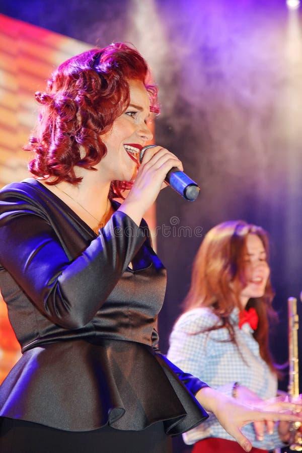 在阶段、音乐家流行音乐石小组薄荷和歌手安娜Malysheva 红色朝向的爵士乐岩石女孩唱歌 免版税图库摄影