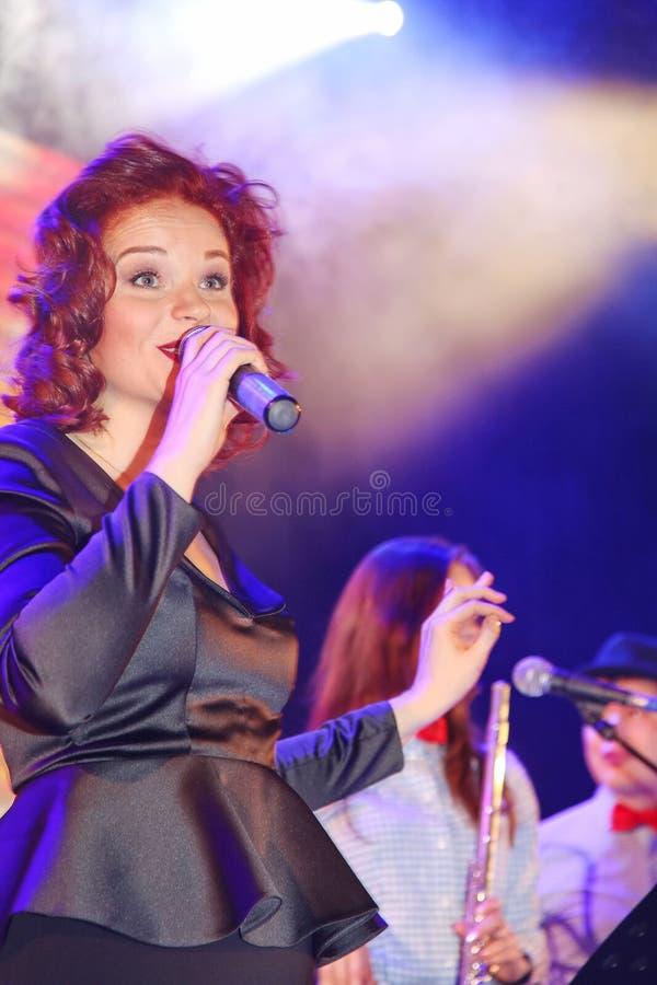 在阶段、音乐家流行音乐石小组薄荷和歌手安娜Malysheva 红色朝向的爵士乐岩石女孩唱歌 免版税库存图片