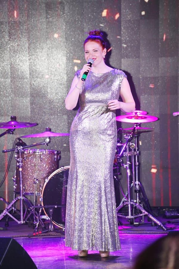 在阶段、音乐家流行音乐石小组薄荷和歌手安娜Malysheva 红色朝向的迷人岩石女孩唱歌 免版税库存照片