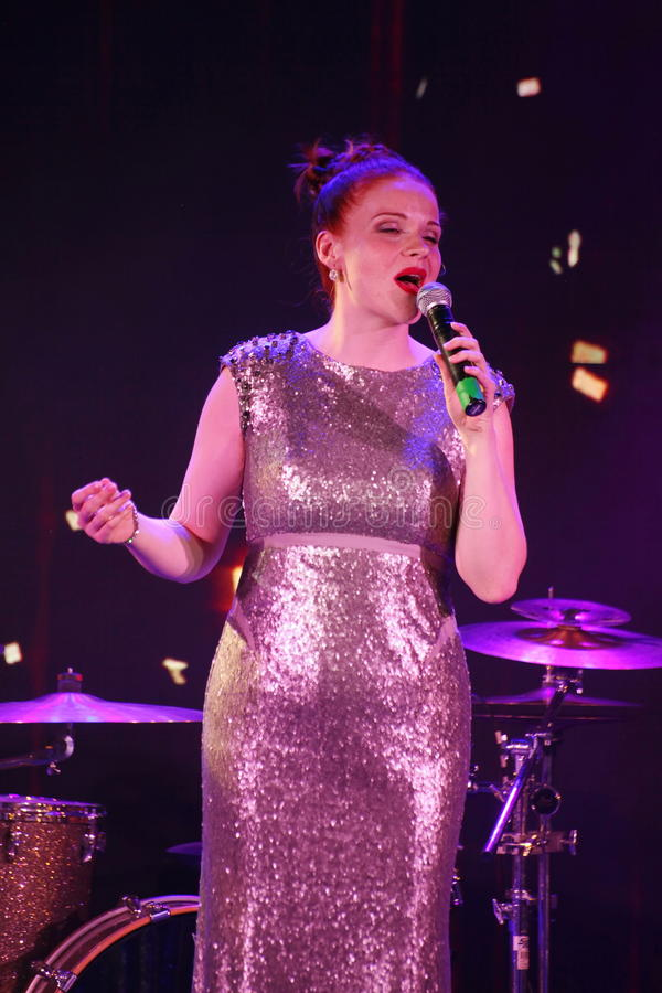 在阶段、音乐家流行音乐石小组薄荷和歌手安娜Malysheva 红色朝向的迷人岩石女孩唱歌 库存照片