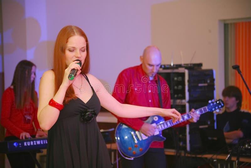 在阶段、音乐家流行音乐石小组薄荷和歌手安娜Malysheva 红色 红色朝向的迷人岩石女孩唱歌 免版税图库摄影