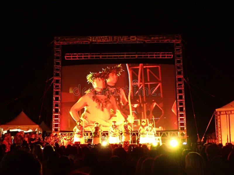在阶段的夏威夷舞蹈家立场在晚上 库存图片