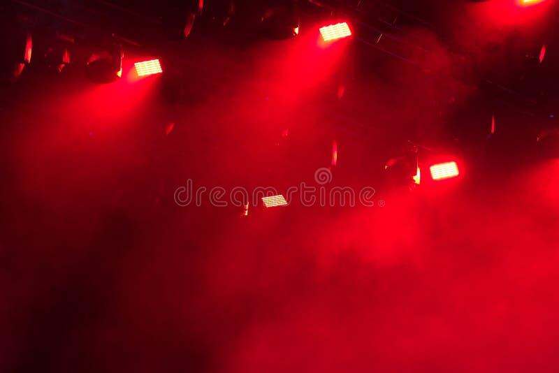 在阶段的红灯照亮的烟 图库摄影