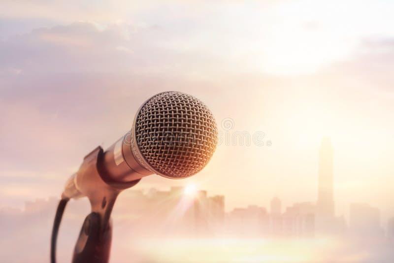 在阶段的话筒在日落城市背景的音乐会 免版税图库摄影