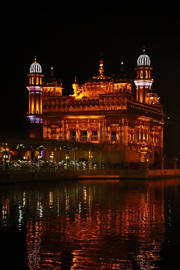 在阿姆利则、旁遮普邦、印度、最神圣的象和锡克教徒的宗教崇拜地方的金黄寺庙  照亮夜, 库存图片
