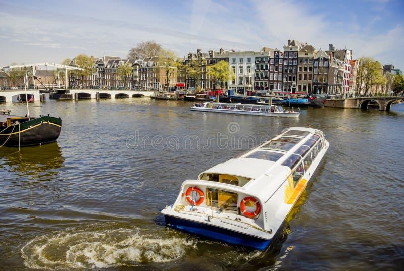 在阿姆斯特丹的看法和Amstel劈裂与巡航小船,下面 免版税库存照片