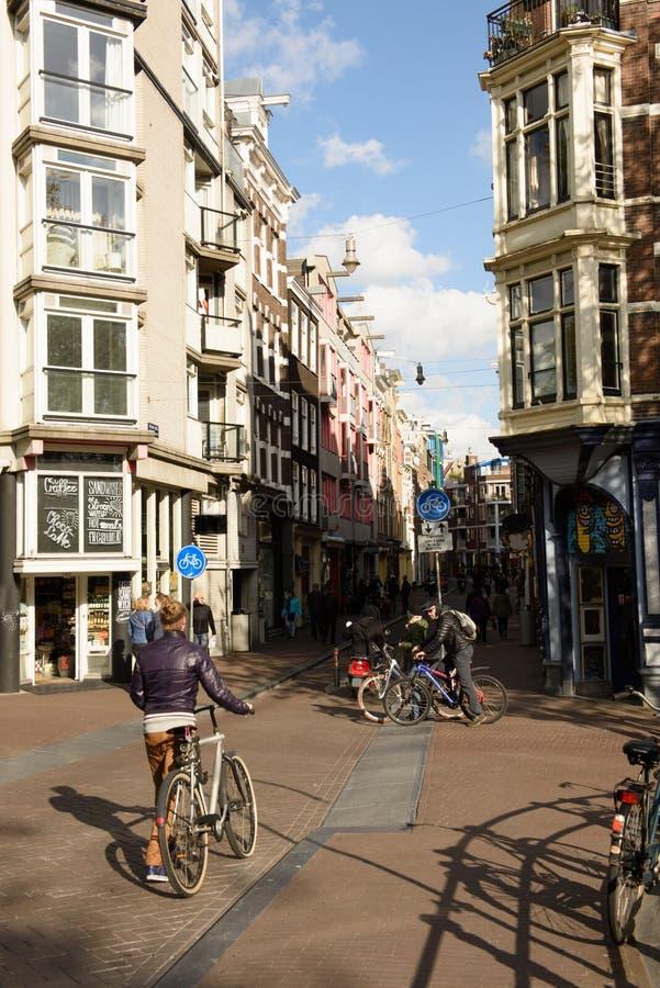 在阿姆斯特丹街道上的自行车骑士在春天 库存图片