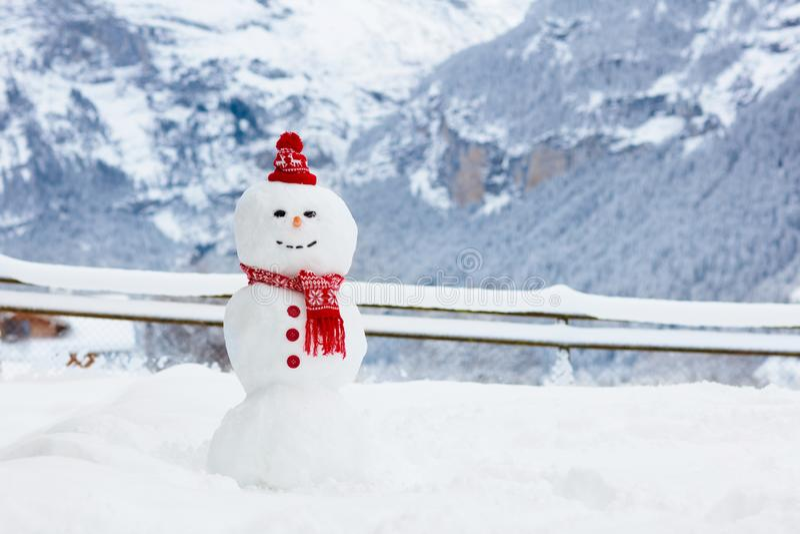 在阿尔卑斯山的雪人 雪人在冬天山风景的大厦乐趣 在多雪的冷天的家庭室外活动 免版税库存照片
