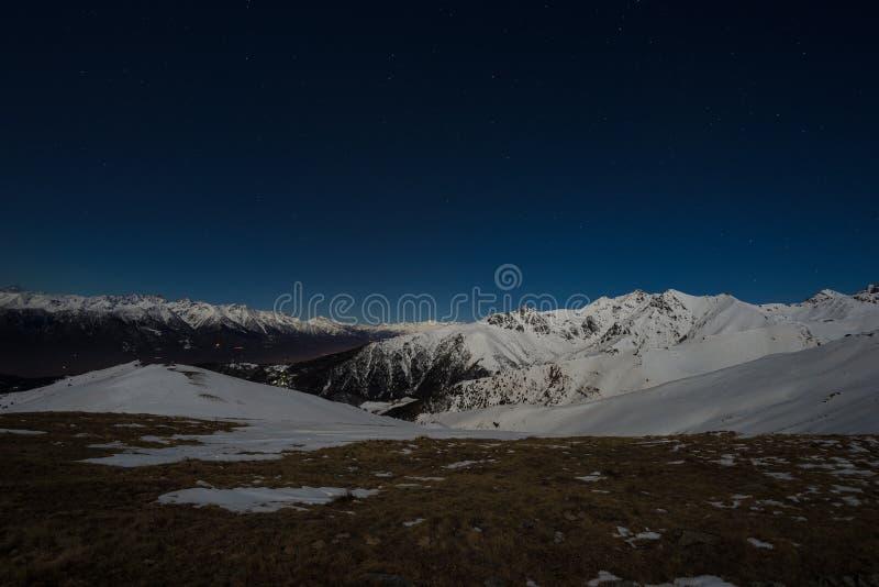 在阿尔卑斯的满天星斗的天空夜视图 雪在月光的加盖的山脉 免版税库存图片