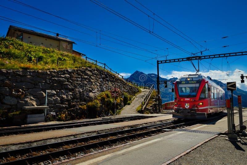 在阿尔卑斯阴郁的火车站, Grisons,瑞士的红色RhB火车 库存照片