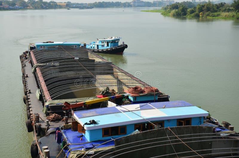 在阿尤特拉利夫雷斯泰国闯入并且用力拖小船货船在Choaphraya河 库存照片