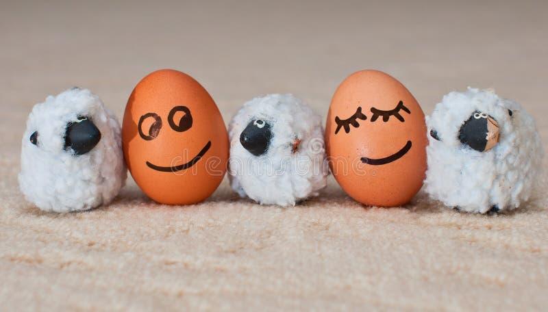 在附近的两个滑稽的微笑的鸡蛋小绵羊 免版税库存图片