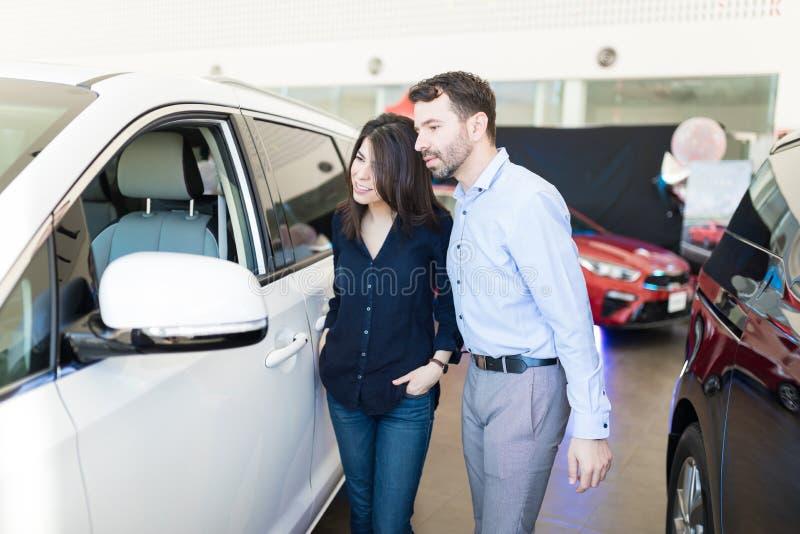 在陈列室结合表示兴趣在白色汽车上 免版税库存图片