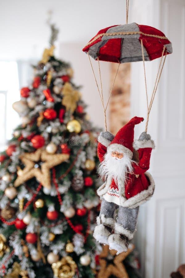 在降伞的圣诞老人玩具带来礼物在红色圣诞树bokeh背景 大Copyspace概念新年横幅 免版税库存图片