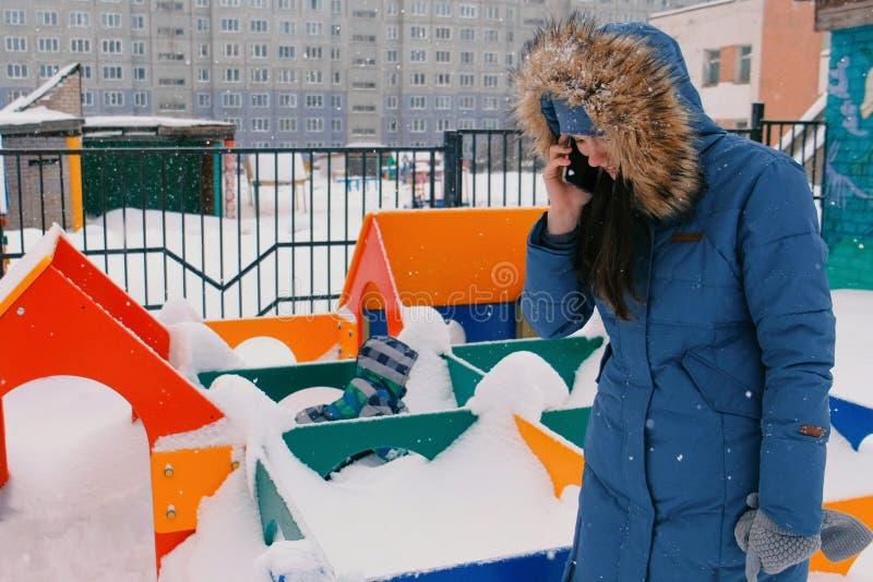 在降雪期间时,当她的儿子在操场走在冬天妈妈在一个手机叫 图库摄影