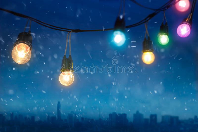在降雪的五颜六色的发光的圣诞灯在深蓝城市 免版税图库摄影