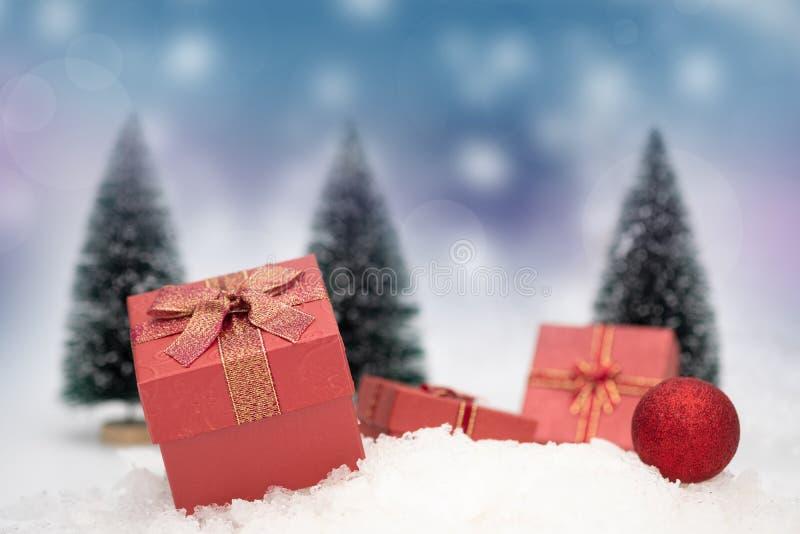 在降雪的红色礼物盒与季节greeti的拷贝空间 免版税库存照片