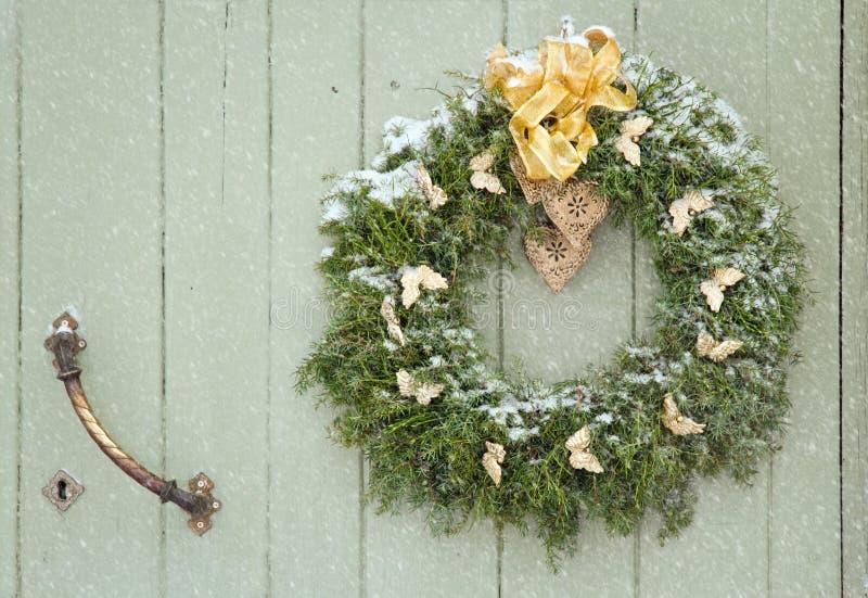 在降雪的绿色圣诞节花圈 免版税库存图片