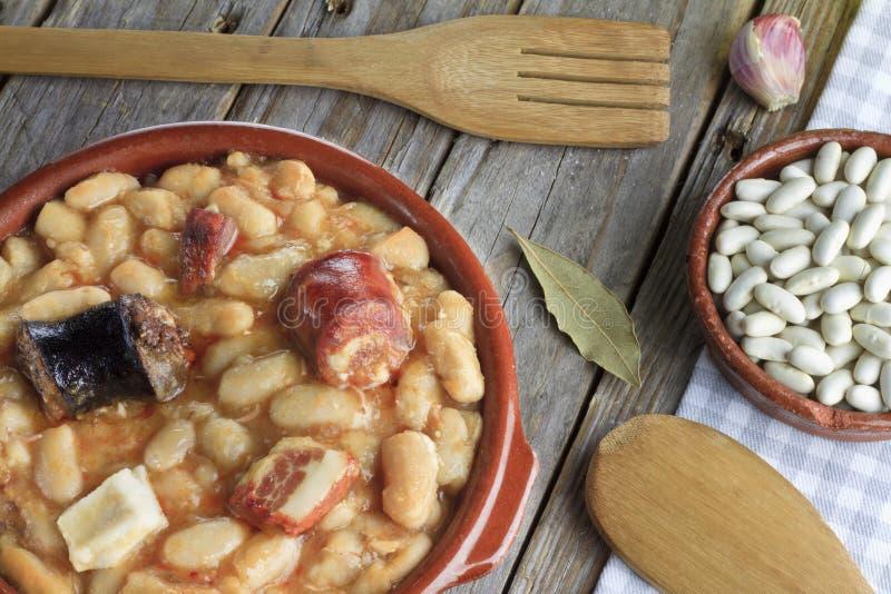 在陶器盘的西班牙fabada和一木叉子和knif 免版税库存照片