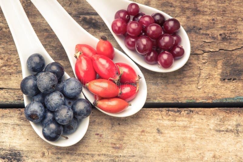 在陶瓷匙子的新鲜的野生莓果在木背景 健康的食物 库存照片