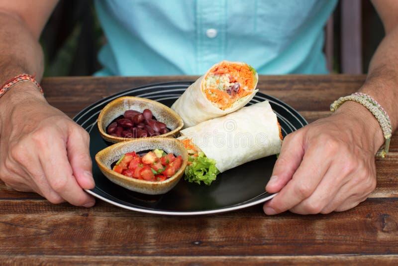 在陶瓷器皿的面卷饼,人吃一个面卷饼,鲜美,它是有用,素食食物 库存图片