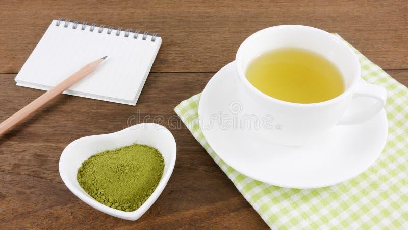 在陶瓷心形的碗和杯子热的绿茶和笔记本的日本matcha绿茶粉末与铅笔 免版税库存图片