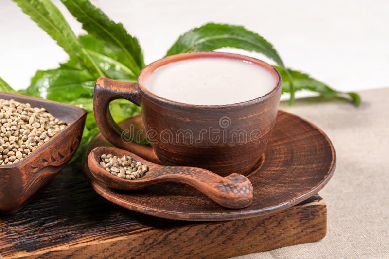 在陶瓷杯子的大麻在棕色陶瓷碗和匙子和大麻叶子的牛奶和五谷 免版税图库摄影