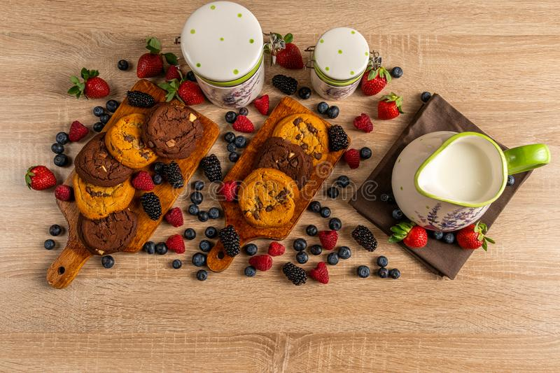 在陶瓷水罐的牛奶用被烘烤的曲奇饼和野生莓果在木桌上 免版税库存图片