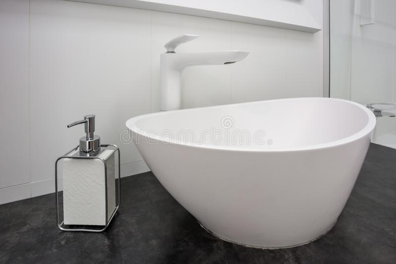在陶瓷水龙头水槽附近的肥皂和香波分配器与龙头在昂贵的顶楼卫生间里 免版税库存照片