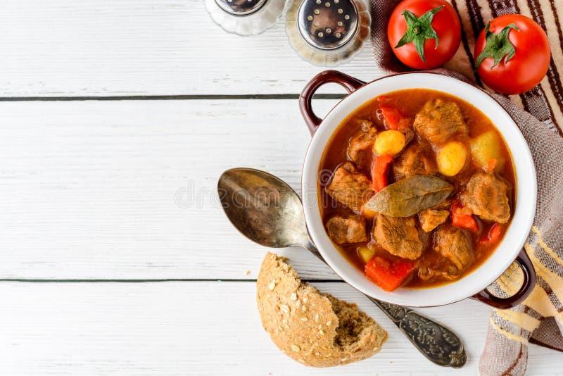 在陶瓷碗的墩牛肉在白色木背景 传统匈牙利汤 免版税图库摄影