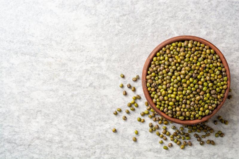 在陶瓷碗的绿色绿豆在灰色石背景 库存图片